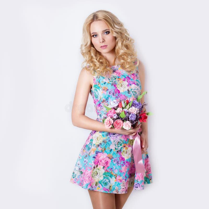 Muchacha blanda dulce modesta atractiva hermosa con el pelo rubio rizado que se coloca en el fondo blanco con un ramo de flores d imagen de archivo libre de regalías