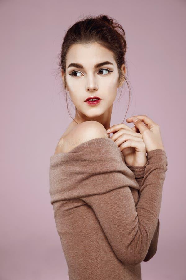 Muchacha blanda hermosa con el maquillaje que presenta en perfil sobre fondo rosado imagenes de archivo