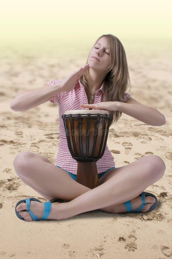 Batería de Djembe que juega en la playa imagenes de archivo