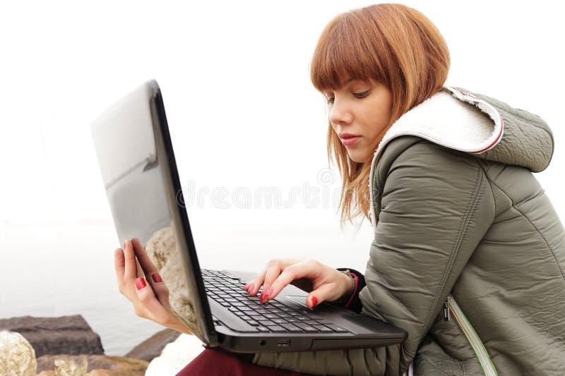 Muchacha bonita con el ordenador portátil foto de archivo libre de regalías