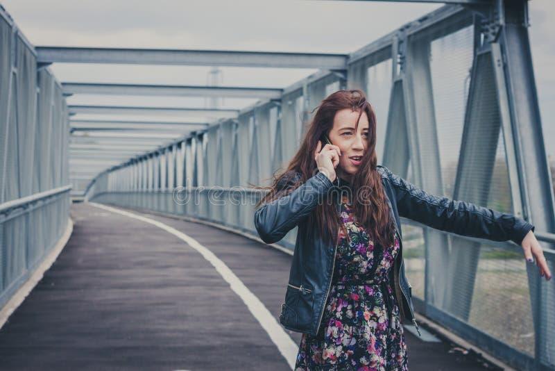 Muchacha bonita con el pelo largo que habla en el teléfono imágenes de archivo libres de regalías
