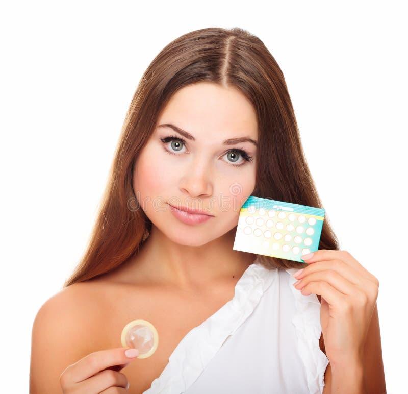 Muchacha bonita con el preservativo y las píldoras anticonceptivas fotografía de archivo libre de regalías