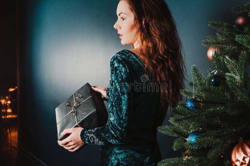Muchacha bonita con la caja de regalo cerca del árbol de navidad, sorprendido imagenes de archivo