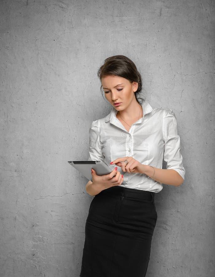 Muchacha bonita con la tableta en sus manos contra imagen de archivo libre de regalías