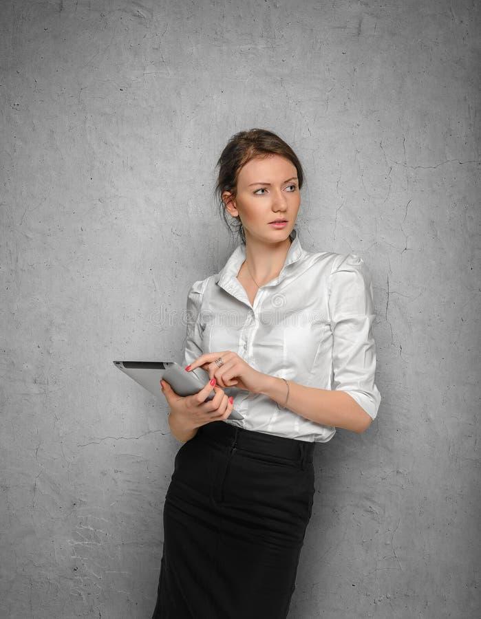 Muchacha bonita con la tableta en sus manos contra imagen de archivo
