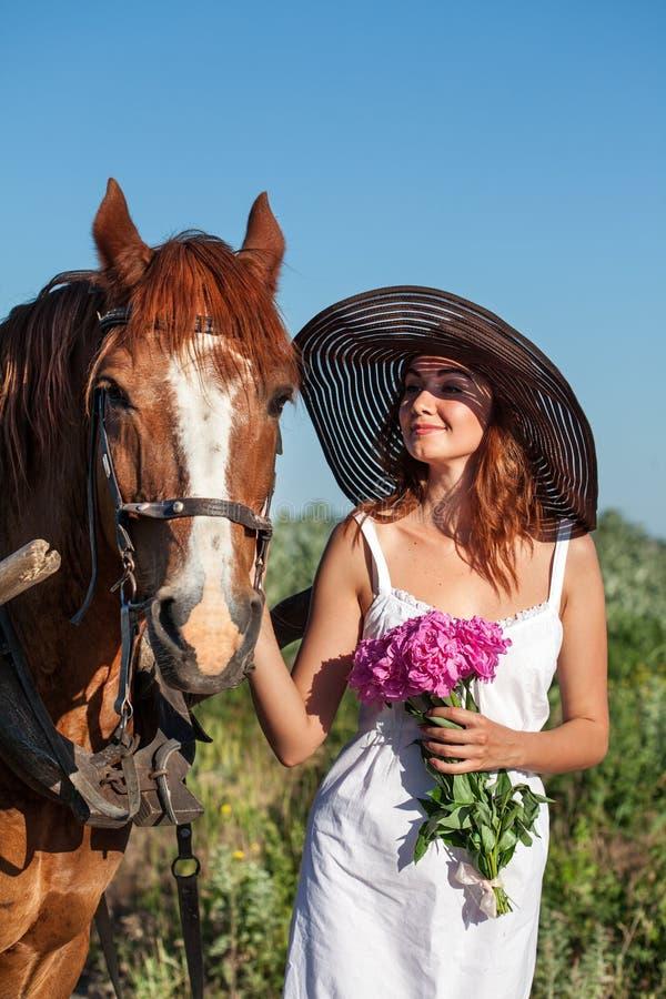 Muchacha bonita con los wildflowers en el carro del caballo en día de verano imagen de archivo