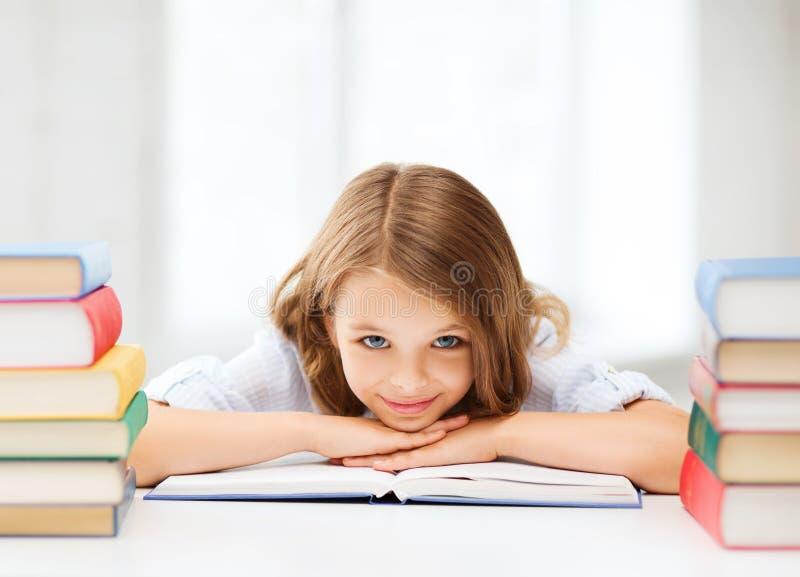 Muchacha bonita con muchos libros en la escuela foto de archivo