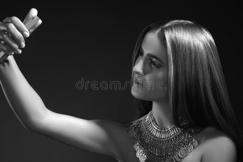 Muchacha bonita de la moda que toma Selfie en el teléfono móvil Estilo con los accesorios, maquillaje de moda, pelo liso largo de foto de archivo