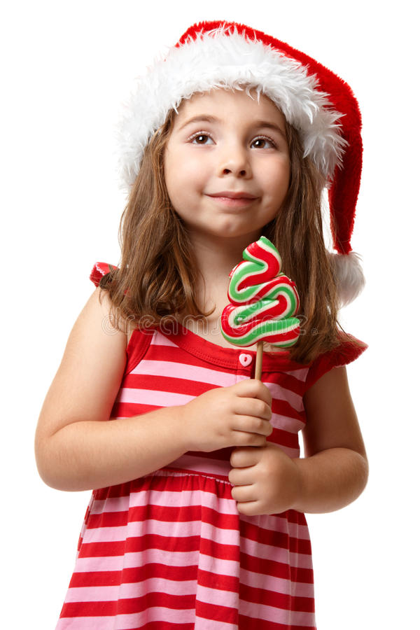 Muchacha bonita de santa con el lollipop de la Navidad imagen de archivo
