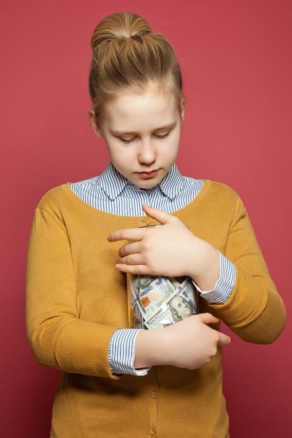 Muchacha bonita del adolescente que mira el tarro de cristal con efectivo del dinero Planeamiento del presupuesto de los niños fotografía de archivo libre de regalías