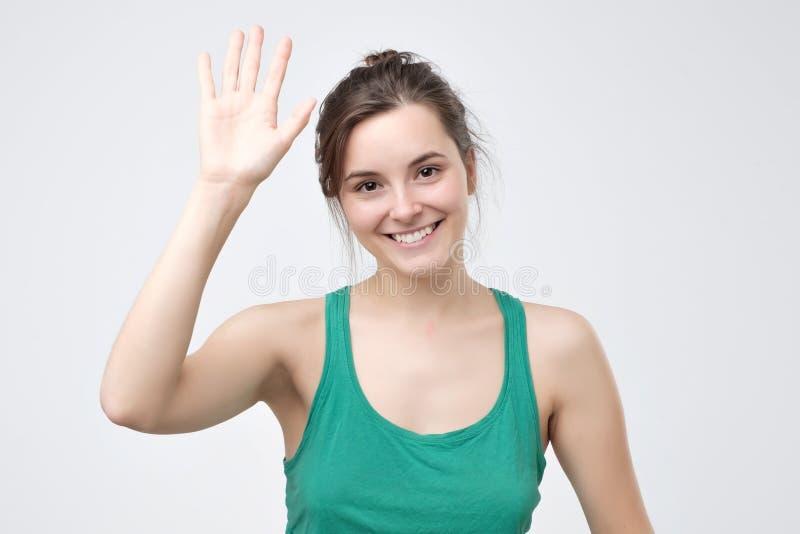 Muchacha bonita del estudiante que dice hola, sonriendo alegre y amistoso, agitando su mano fotos de archivo