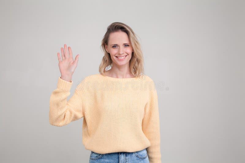Muchacha bonita del estudiante que dice hola, sonriendo alegre y amistoso, agitando su mano actitudes contra fondo gris expresión fotos de archivo