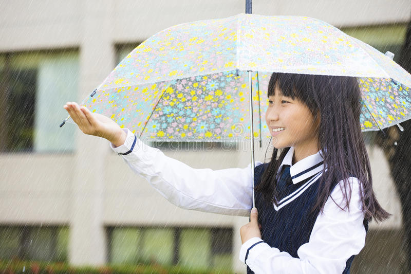 Muchacha bonita del estudiante que sostiene el paraguas en la lluvia fotografía de archivo libre de regalías