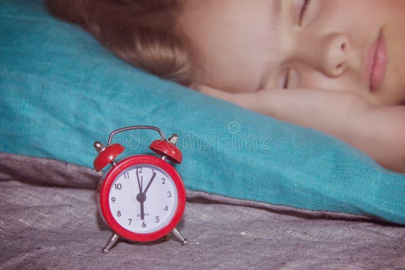 Muchacha bonita del niño que duerme en el fondo de un despertador rojo que la despertará para arriba por la mañana foto de archivo