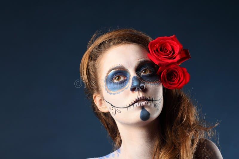 Muchacha bonita del zombi con la cara pintada y dos rosas rojas fotos de archivo