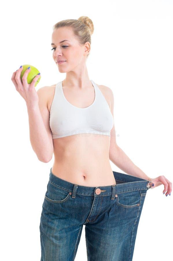 Muchacha bonita deportiva que muestra los pantalones y la manzana grandes Concepto del deporte, de la aptitud y de la dieta Aisla fotos de archivo libres de regalías