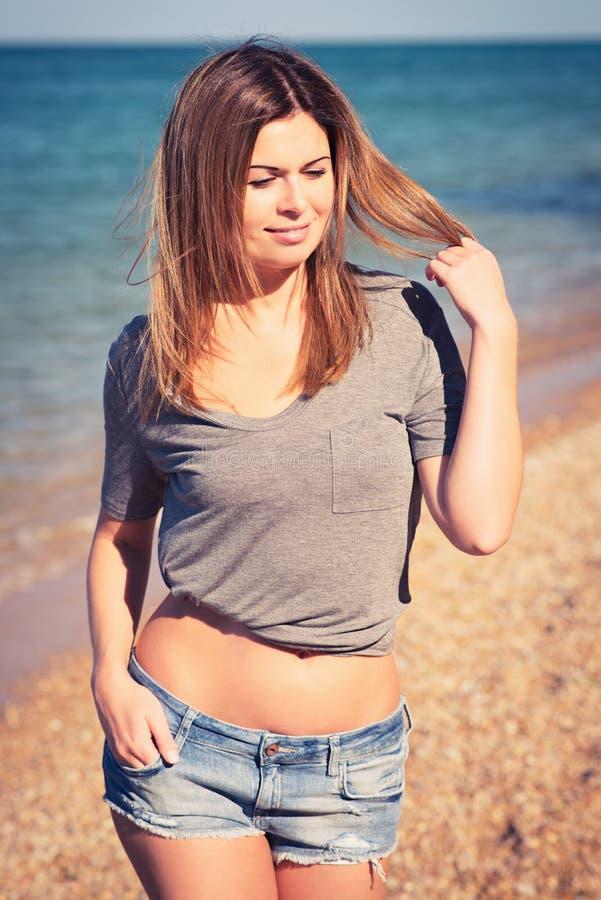 Muchacha bonita en los pantalones cortos atractivos que presentan en la playa imágenes de archivo libres de regalías