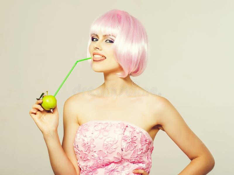 Muchacha bonita en peluca rosada con la manzana verde imagen de archivo
