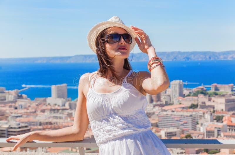 Muchacha bonita en un sombrero y las gafas de sol que presentan contra la ciudad de imagen de archivo