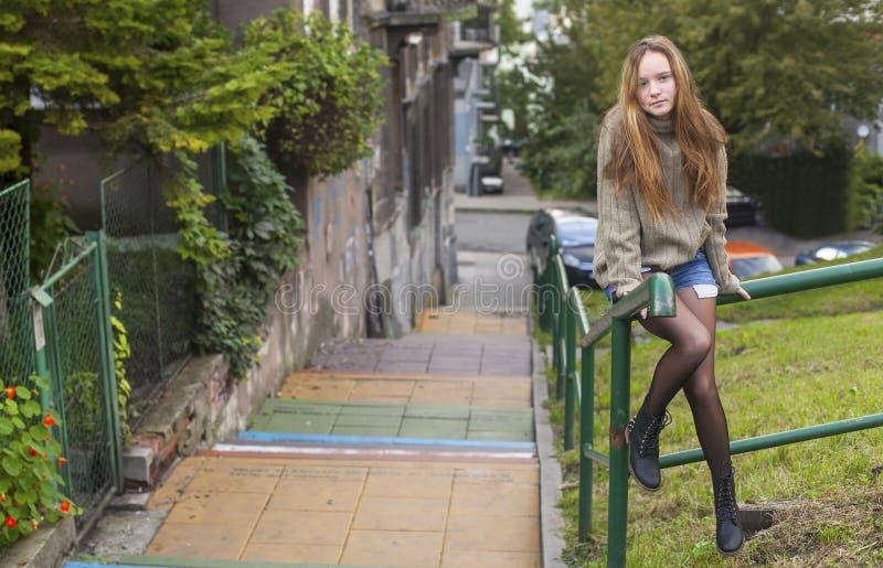 Muchacha bonita en un suéter que se sienta en las escaleras de una calle de la verja imagenes de archivo