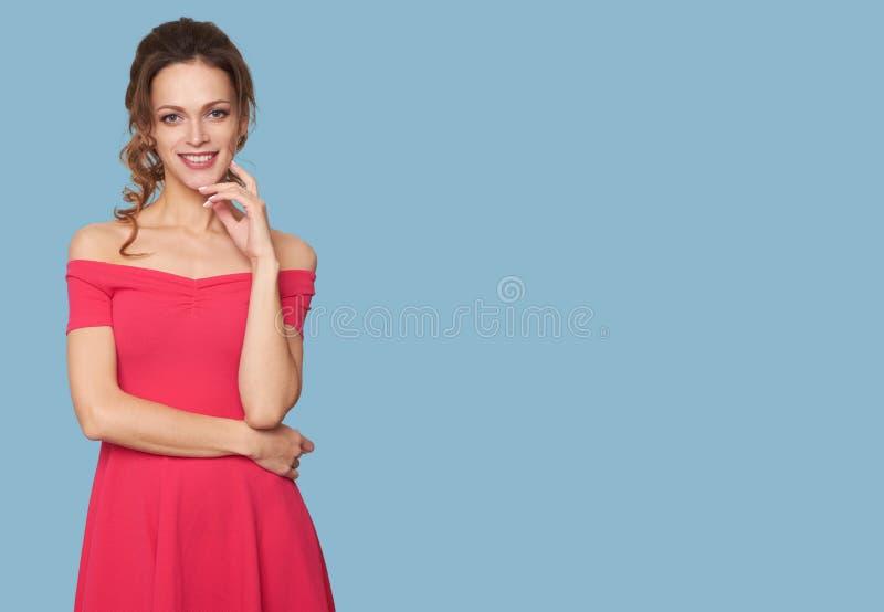Muchacha bonita en vestido rojo del verano Aislado en azul foto de archivo