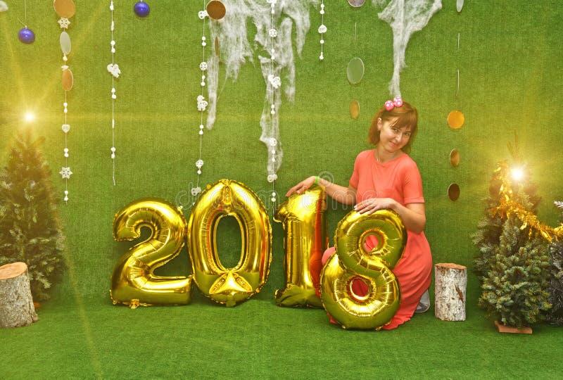 Muchacha bonita hermosa en vestido con números del Año Nuevo 2018 y fotografía de archivo