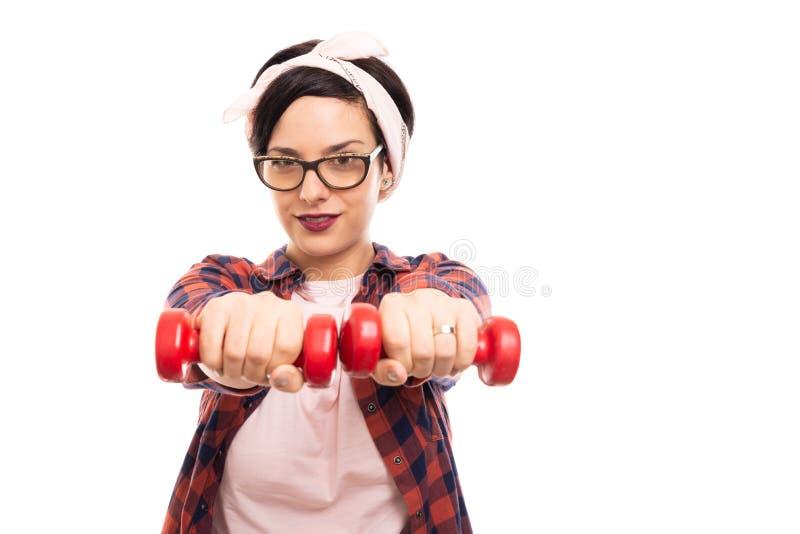 Muchacha bonita joven del perno-para arriba que trabaja con pesa de gimnasia de dos rojos imagenes de archivo