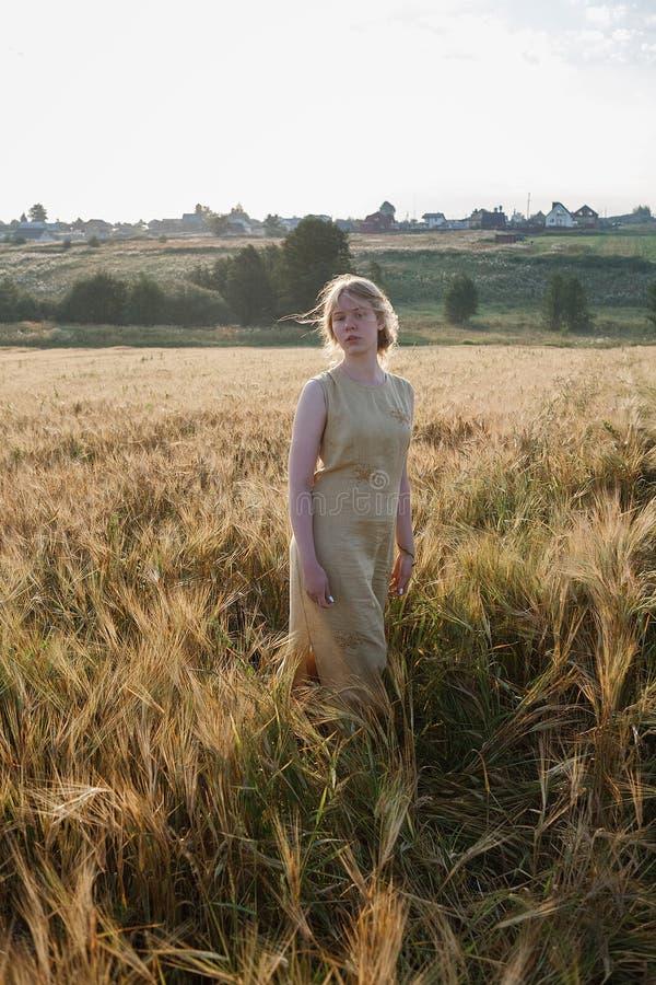 Muchacha bonita joven en soportes amarillos del vestido en el campo de oídos en rayos del sol naciente arboleda y pueblo en fondo fotografía de archivo libre de regalías