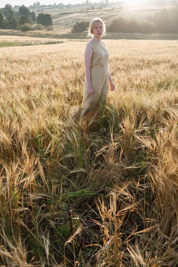 Muchacha bonita joven en soportes amarillos del vestido en el campo de oídos en rayos del sol naciente arboleda y pueblo en fondo imagen de archivo libre de regalías