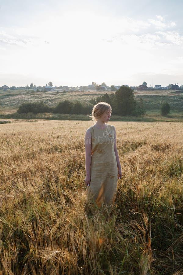 Muchacha bonita joven en soportes amarillos del vestido en el campo de oídos en rayos del sol naciente arboleda y pueblo en fondo fotografía de archivo