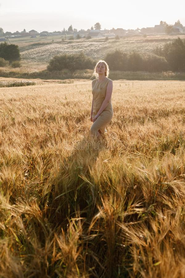 Muchacha bonita joven en soportes amarillos del vestido en el campo de oídos en rayos del sol naciente arboleda y pueblo en fondo foto de archivo