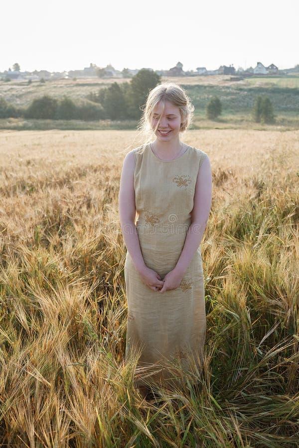 Muchacha bonita joven en soportes amarillos del vestido en el campo de oídos en rayos del sol naciente arboleda y pueblo en fondo fotos de archivo libres de regalías