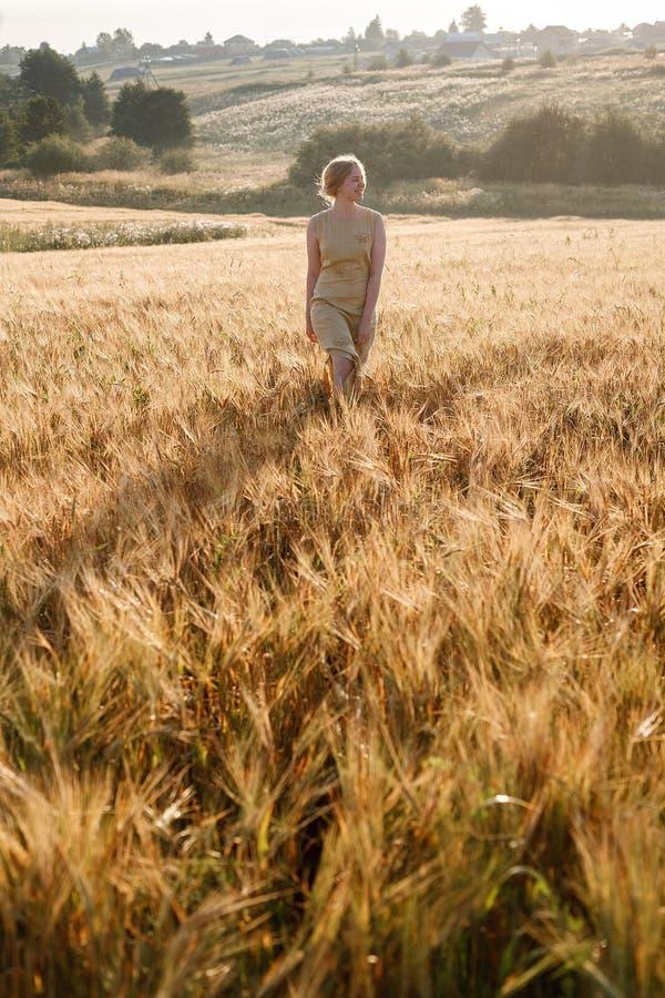 Muchacha bonita joven en soportes amarillos del vestido en el campo de oídos en rayos del sol naciente arboleda y pueblo en fondo imagen de archivo