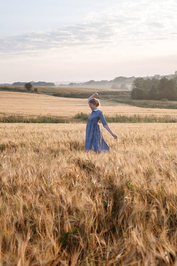 Muchacha bonita joven en vestido azul con las actitudes recogidas del pelo, caminando en el campo de oídos en la salida del sol A foto de archivo libre de regalías