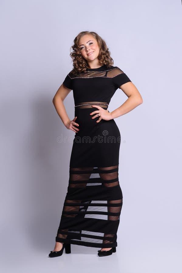 Muchacha bonita joven en vestido Imagen del estudio, fondo gris fotos de archivo libres de regalías