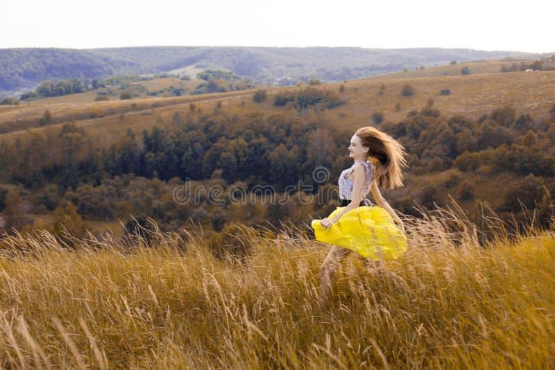 Muchacha bonita joven juguetona feliz que corre en el campo con trigo verde, amarillo en la manera a la buena vida Aventura feliz imagen de archivo libre de regalías
