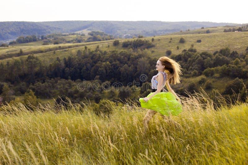 Muchacha bonita joven juguetona feliz que corre en el campo con trigo verde, amarillo en la manera a la buena vida Aventura feliz imágenes de archivo libres de regalías
