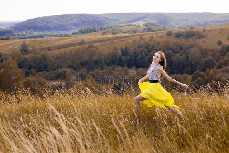 Muchacha bonita joven juguetona feliz que corre en el campo con trigo verde, amarillo en la manera a la buena vida Aventura feliz fotografía de archivo libre de regalías