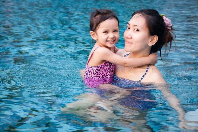 Muchacha bonita joven que juega con su madre en piscina con el wat claro fotografía de archivo