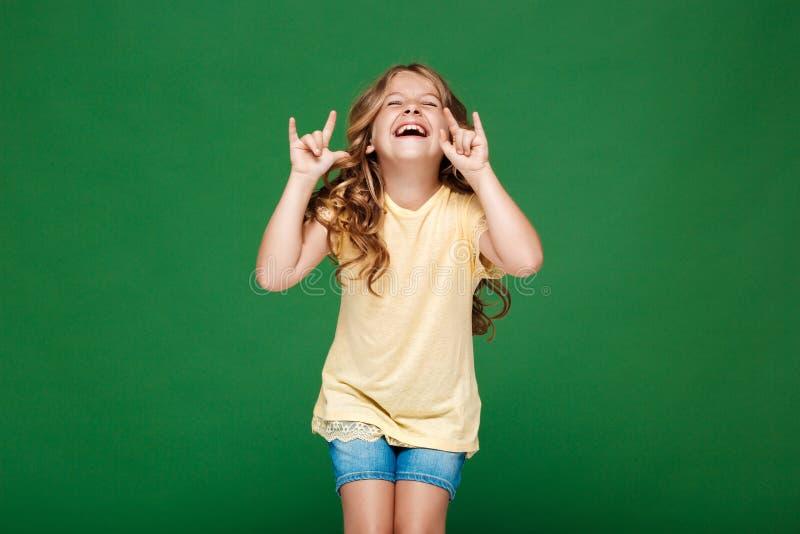 Muchacha bonita joven que ríe sobre fondo verde imágenes de archivo libres de regalías