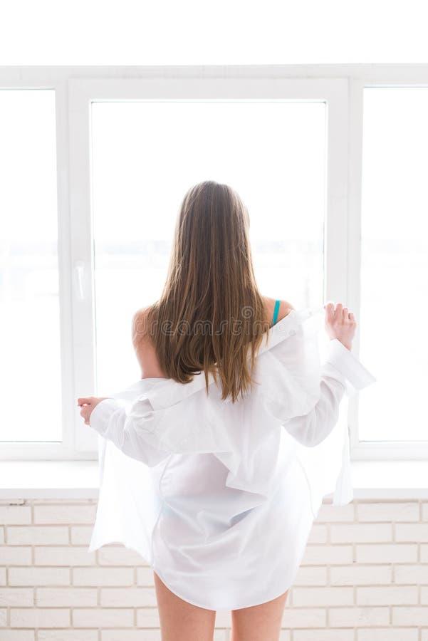 Muchacha bonita joven unclothing una camisa blanca de los men's cerca de la ventana fotos de archivo