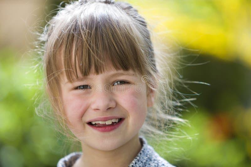 Muchacha bonita linda del ni?o con los ojos grises y el pelo justo que sonr?e in camera al aire libre en verde soleado borroso y  fotografía de archivo libre de regalías