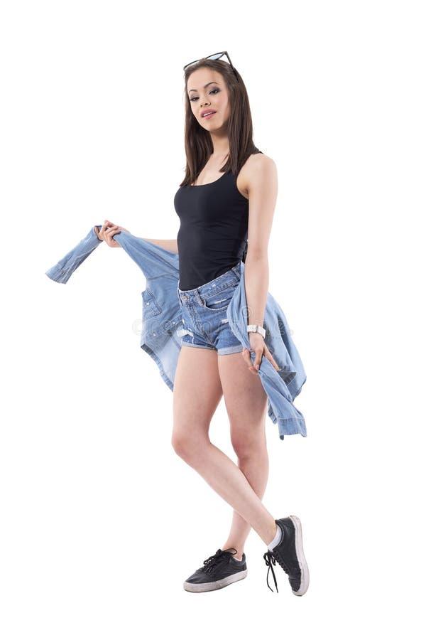 Muchacha bonita milenaria de moda confiada que ata la chaqueta de los vaqueros alrededor de las caderas que miran la cámara foto de archivo libre de regalías