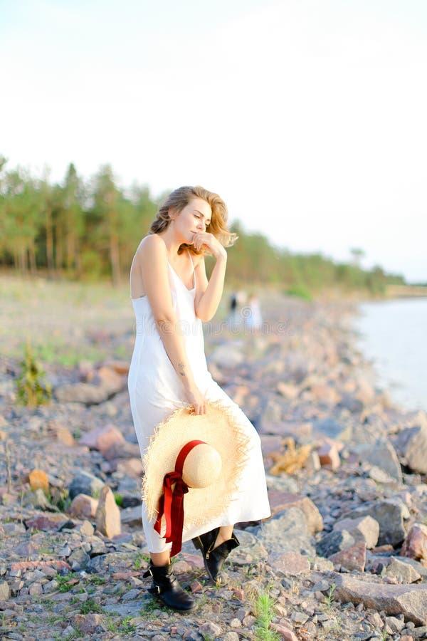 Muchacha bonita que camina en la playa de la tabla con hant en manos y vestido que lleva imágenes de archivo libres de regalías