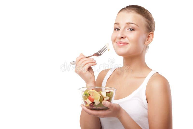 Muchacha bonita que come la ensalada de fruta aislada imágenes de archivo libres de regalías