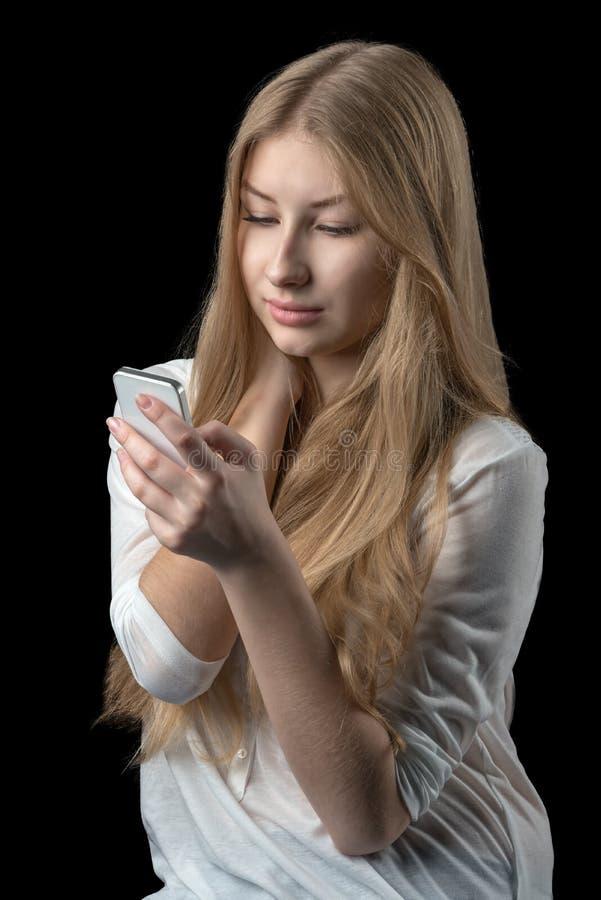 Muchacha bonita que disfruta de la red social en su teléfono móvil imágenes de archivo libres de regalías