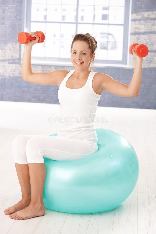 Muchacha bonita que ejercita con pesas de gimnasia en fitball foto de archivo