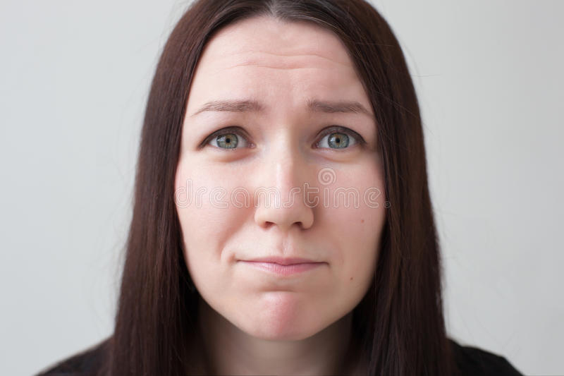 Muchacha bonita que pide algo, frunciendo el ceño su cara fotografía de archivo