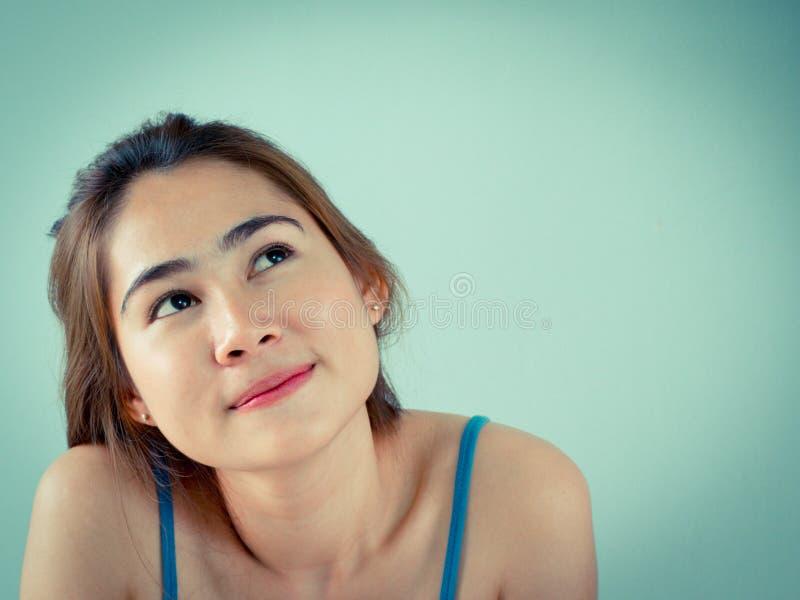Muchacha bonita que piensa y que mira para arriba fotografía de archivo libre de regalías