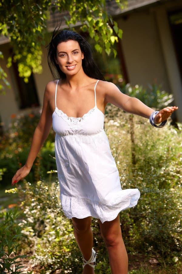Muchacha bonita que se divierte en el jardín en el verano foto de archivo libre de regalías